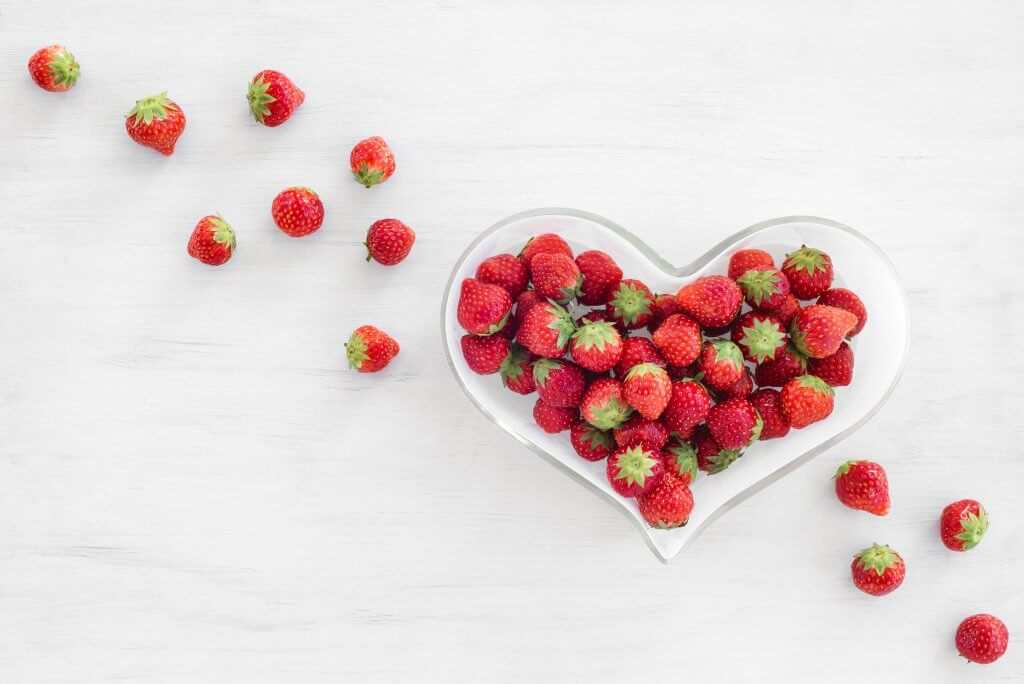 Strawberries in a heart-shaped bowl, on white wooden background.